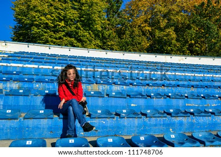 Girl sitting on an empty sports tribune with a camera in her hand. - stock photo
