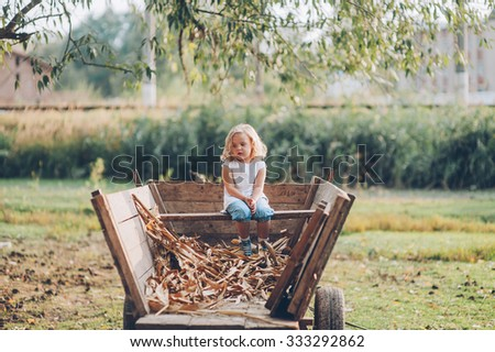 girl sitting on an old wooden wagon in the village