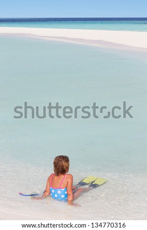 Girl Sitting On Beach Wearing Snorkel And Flippers - stock photo