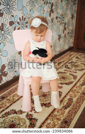 girl sitting on chair and holding rabbit - stock photo