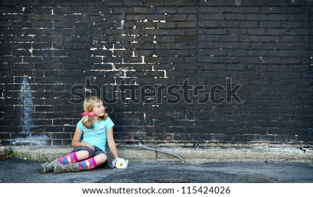 Girl sitting on ground holding flowers next to brick wall - stock photo