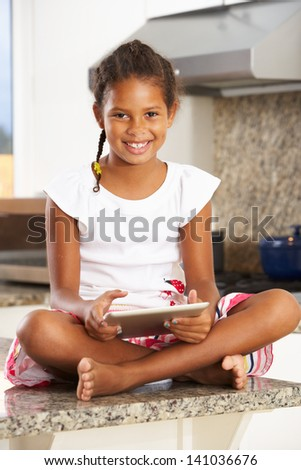 Girl Sitting On Kitchen Counter With Digital Tablet