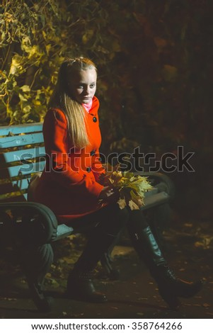 Girl sitting on the bench - stock photo