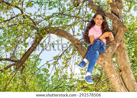 Girl sitting on the bench of tree in forest alone - stock photo