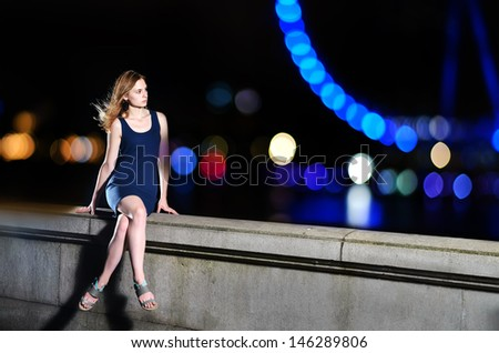 Girl sitting on the border and looking to a night landscape - stock photo
