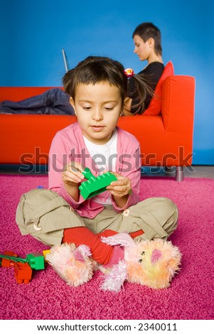 girl sitting on the carpet and playing blocks and  her busy (with laptop) mother on the sofa - stock photo