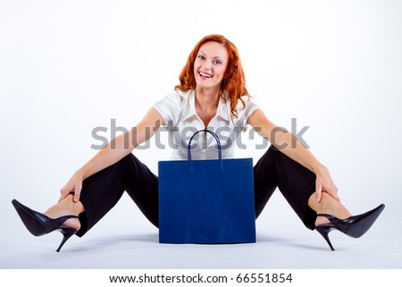 GIRL sitting on the floor in white blouse with blue bags HAVING FUN ON A SHOPPING DAY OUT