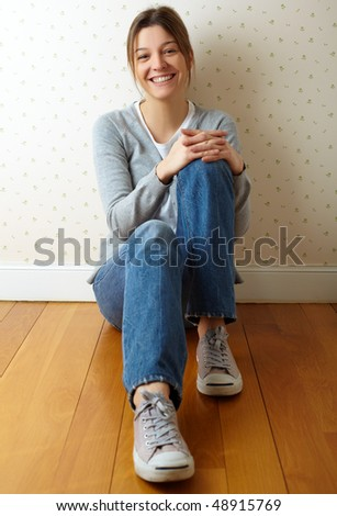 girl sitting on the floor smiling - stock photo