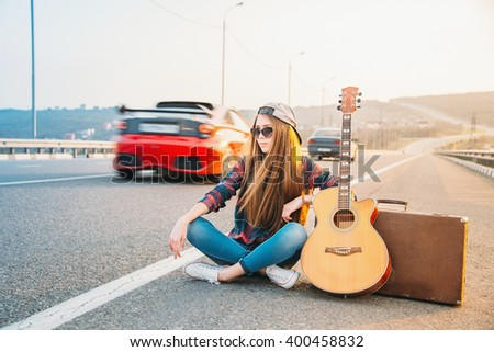 Girl sitting on the pavement with a guitar. Hitchhiking. Image with effects of sunlight - stock photo