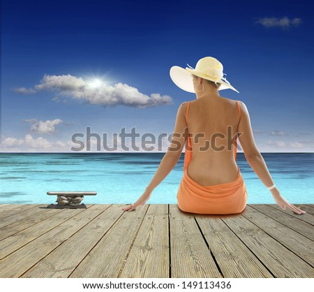 girl sitting on the pier. Ocean View - stock photo