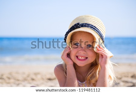 Girl sitting on the sand by the sea - stock photo