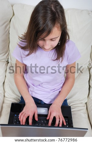 Girl sitting on the sofa and using laptop