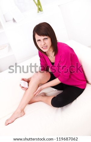 Girl sitting on the sofa having pain while depilating
