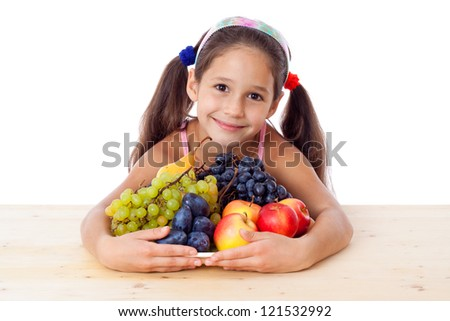 Girl sitting on the table with pile of fruit, isolated on white