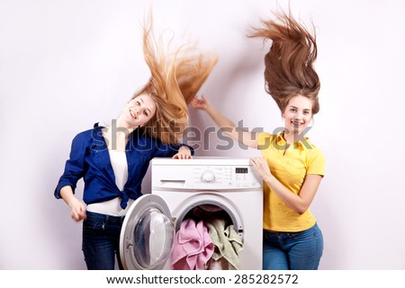 Girl sitting on the washing machine with the laundry for washing