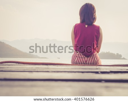 Girl sitting on wood balcony, with sea and mountain; vintage filtered - stock photo