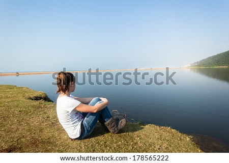 Girl Sitting River Water Lagoon Teen girl relax sitting by beach river lagoon waters on a calm blue day in the countryside - stock photo