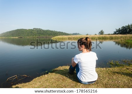 Girl Sitting River Water Lagoon Teen girl relaxing sitting by beach river lagoon waters on a calm blue day in the countryside - stock photo