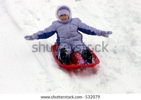 Girl sledding down hill - stock photo