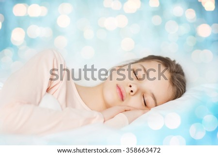 girl sleeping in bed over blue lights background - stock photo
