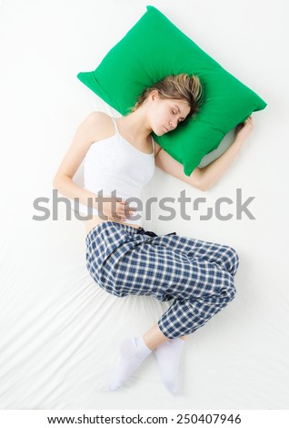 Girl sleeping on a white bed. Top view.