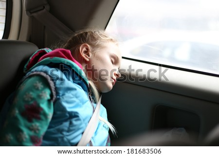 Girl sleeping relaxed and protected in car - stock photo
