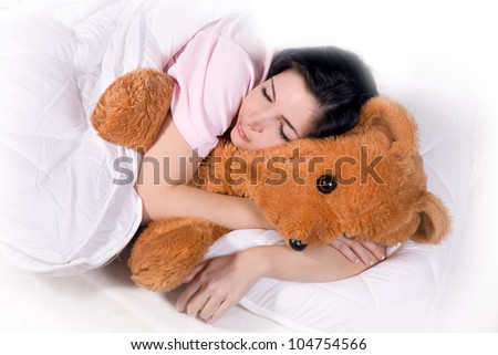 Girl sleeping with teddy bear in bed. Cute girl in nightie lying in bed with plush. A lovely girl sleeping in bed with a toy. Teenager hugging a large teddy bear when sleep in the bed.