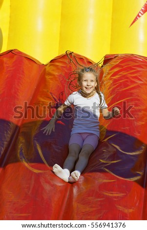 Girl slides down a hill on an inflatable