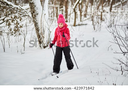 Girl slides on skis through the snowy forest. - stock photo