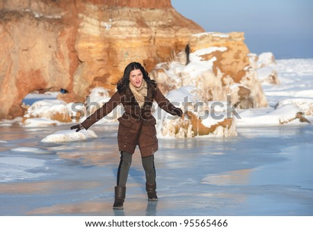 Girl slipping on the ice in sunny winter day