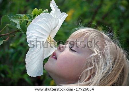 girl smelling hibiscus - stock photo