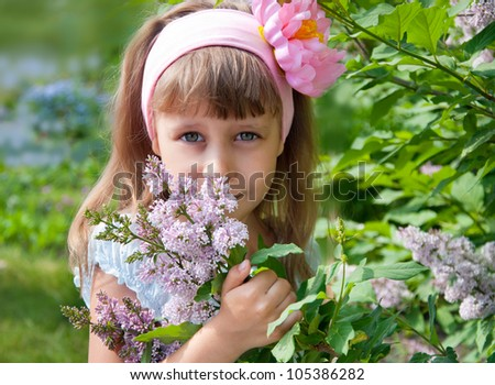 Girl smelling lilac flowers in the garden