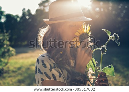 Girl smells sunflower in nature - stock photo
