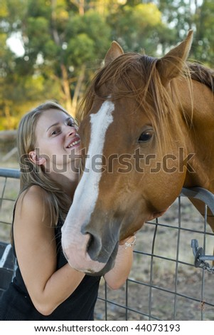Girl smiles with horse in sunset scene - stock photo