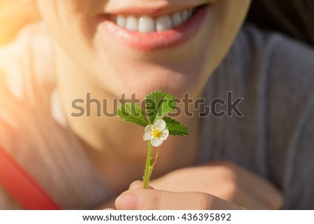 Girl smiling and holding a sprout of strawberry