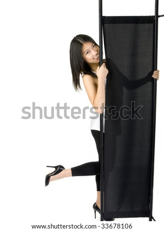 girl smiling from behind folding screen