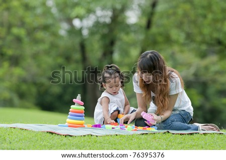 Girl smiling happily on the grass between the play toys  with her mother - stock photo