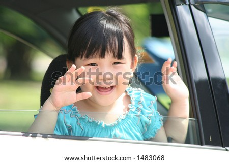Girl smiling & waving goodbye in a car. - stock photo