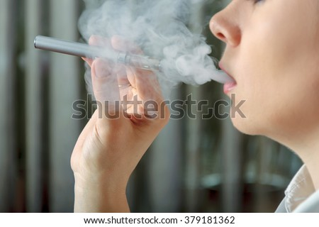 Girl smokes an electronic cigarette and exhaling flavored steam. Concept: safe way of smoking, how to stop smoking - stock photo