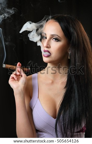 Girl Smoking a cigar .Thick white smoke on black background.