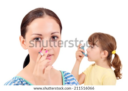 girl smoking cigarette and little girl with inhaler - stock photo