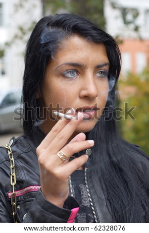 Girl smoking outdoors. More images of this models you can find in my portfolio - stock photo