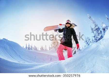 Girl snowboarder goes through snowdrift and holds  snowboard in hands. Sheregesh resort, Siberia, Russia - stock photo