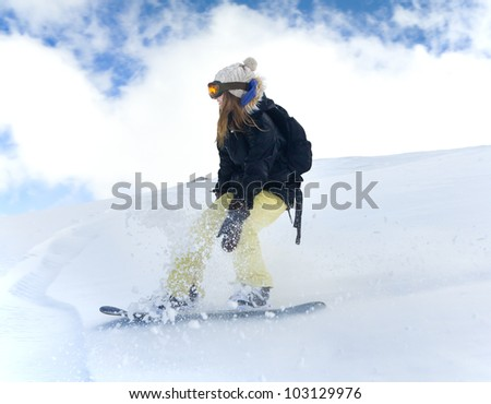 girl snowboarder in motion on snowboard in mountains - stock photo