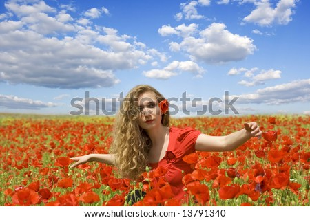 girl spreading her arms in the middle of a poppy field with blue cloudy sky, 'enjoying summer time' - stock photo