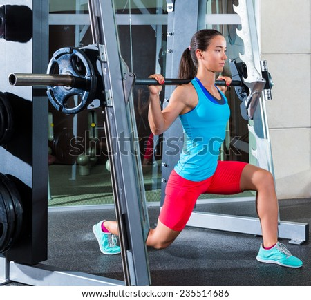 girl squats in multipower squatting smith machine barbell at gym smith - stock photo