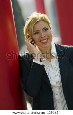 girl standing alone in Milan while talking at her mobile - stock photo