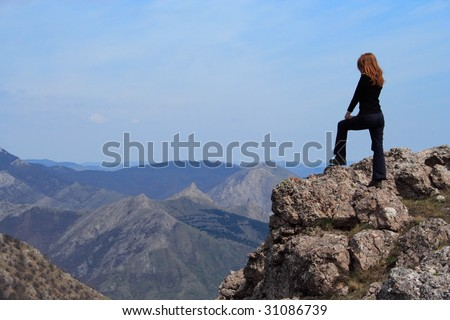 girl standing at the edge of rock - stock photo