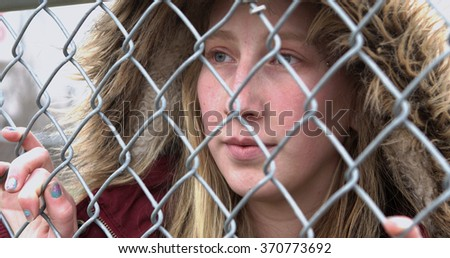 Girl standing behind fence with sadness in her eyes - stock photo