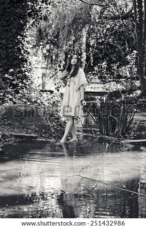 Girl standing by a stream (black and white)